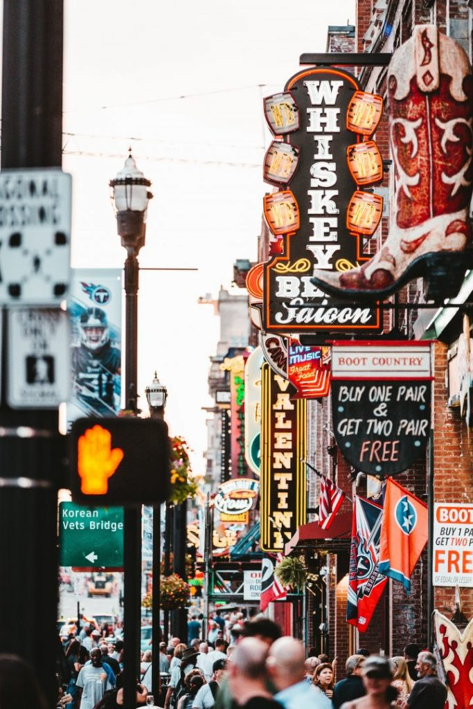 a busy street with neon signs in Nashville