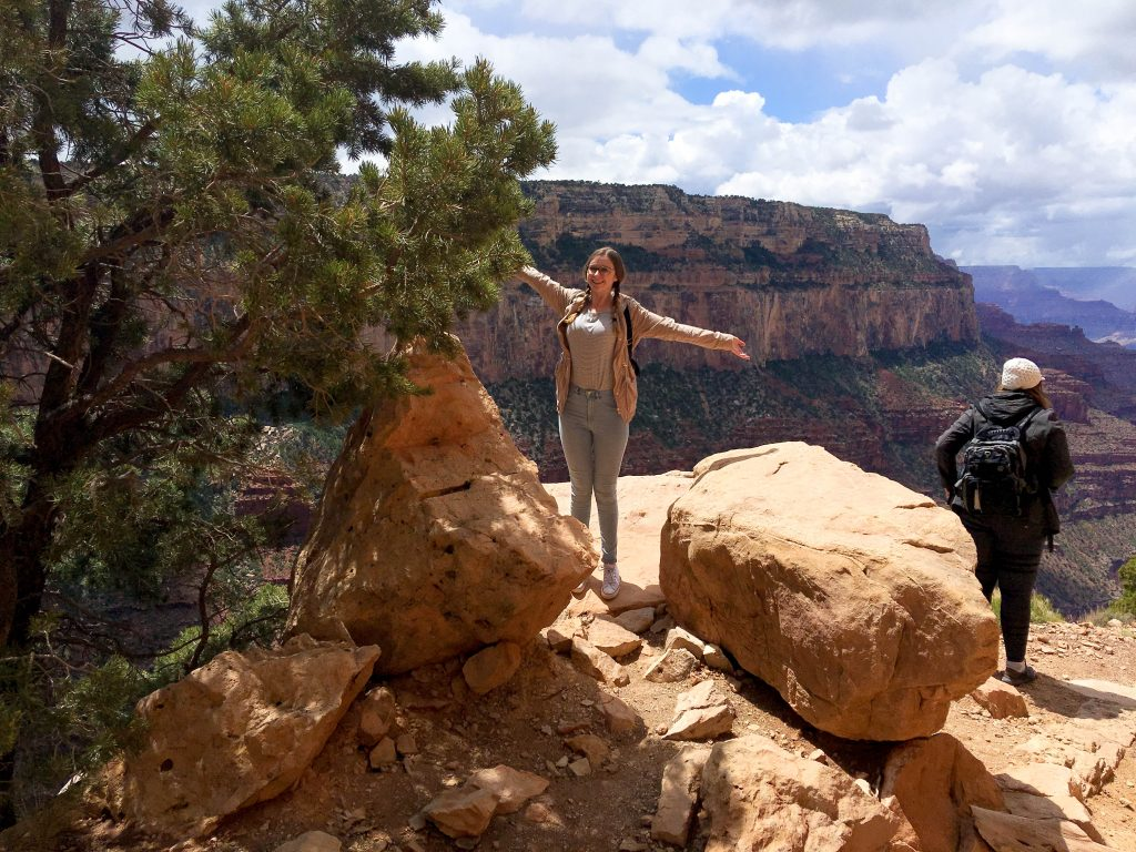 Addie standing with her arms out on the rim of the Grand Canyon