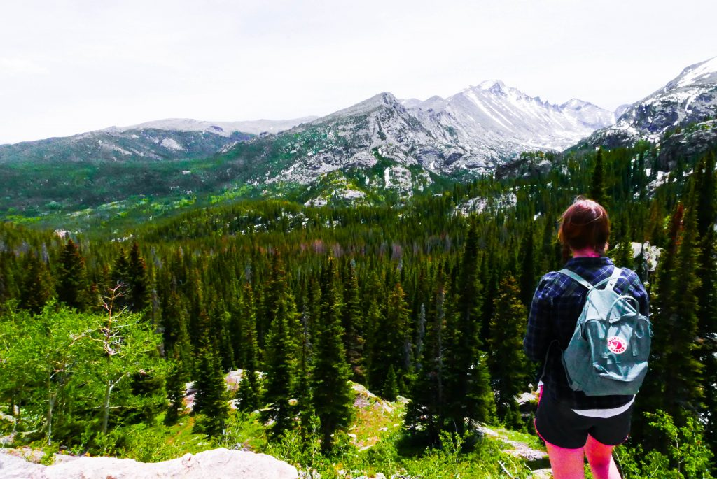 A girl with a blue backpack staring out at the Rocky mountains - the perfect day trip for a Denver itinerary