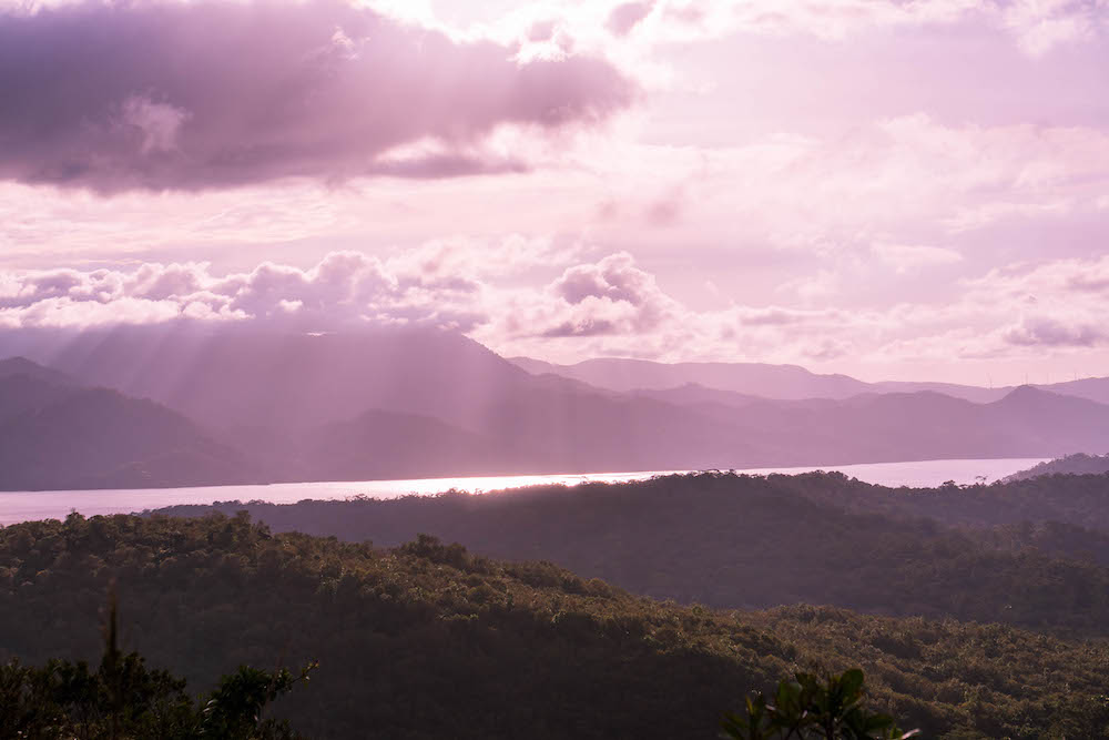 A beautiful purple sunset over Lake Arenal in La Fortuna, Costa Rica with mountains in the background