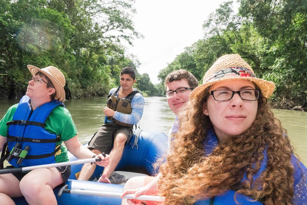 A group of people sitting on a raft on a wildlife rafting safari -- one of the best things to do in La Fortuna, Costa Rica