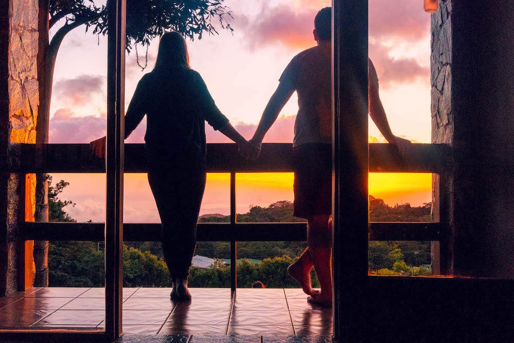 A girl and boy holding hands on a balcony, looking out at the sunset