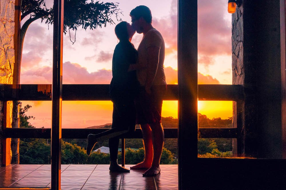 Addie and Daniel kissing on a balcony in front of the sunset in Monteverde