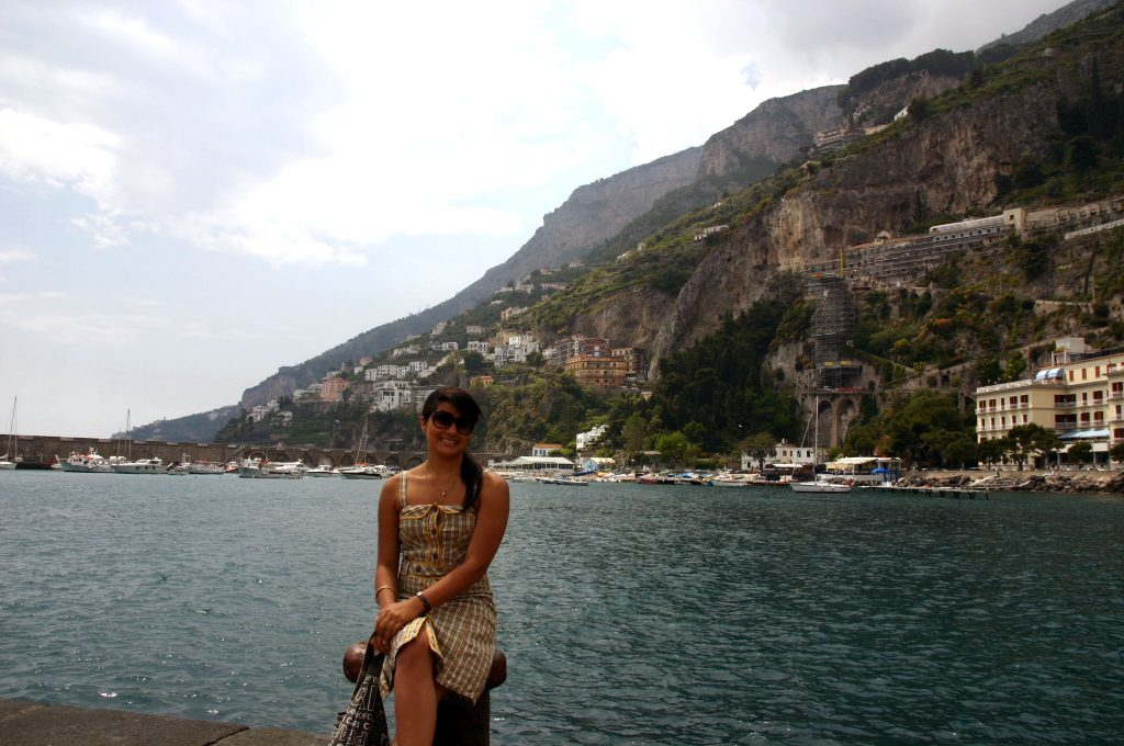 Girl sitting on a bunch by a lake while studying abroad in Italy