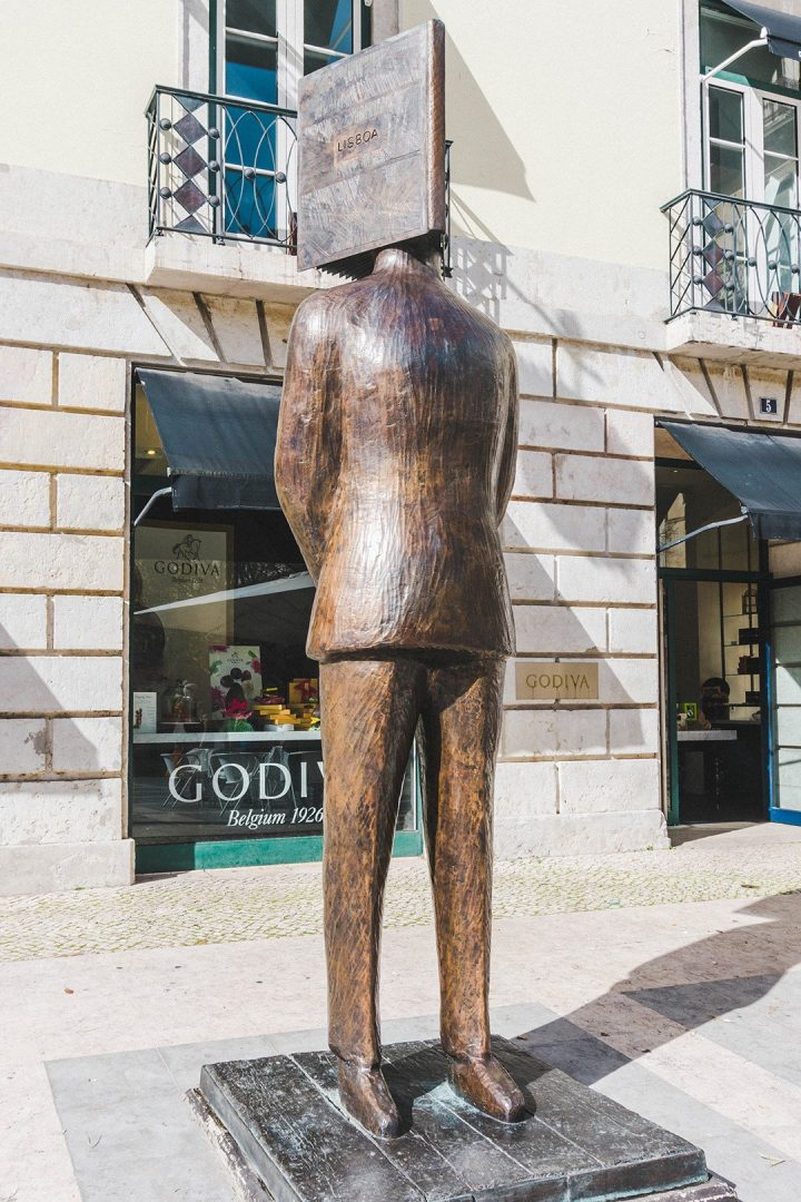 A statue of a man with his head in a book in Lisbon, Portugal