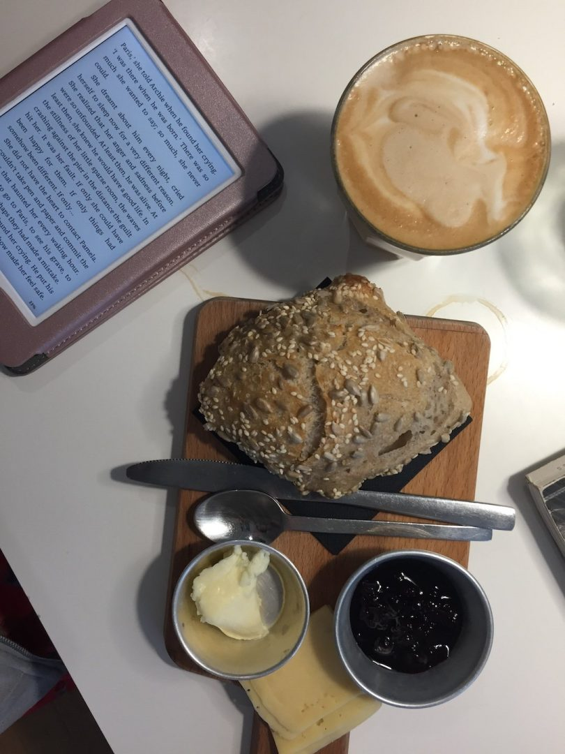A Latte, Bread and jam, and a kindle at Copenhagen Coffee Lab in Lisbon, Portugal