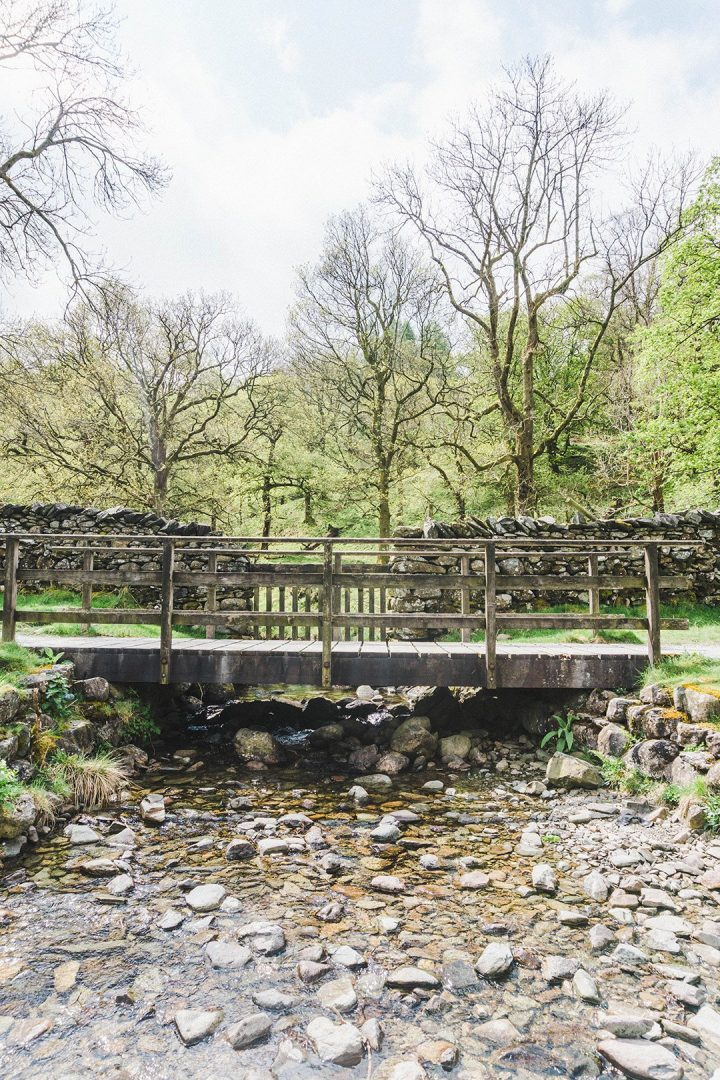 A cute wooden bridge over a small river in the Lake District, UK