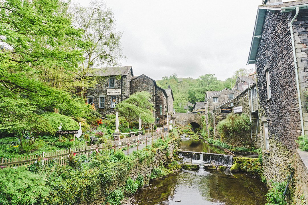 The river running through Ambleside in the Lake District, UK, with stone houses lining the shore