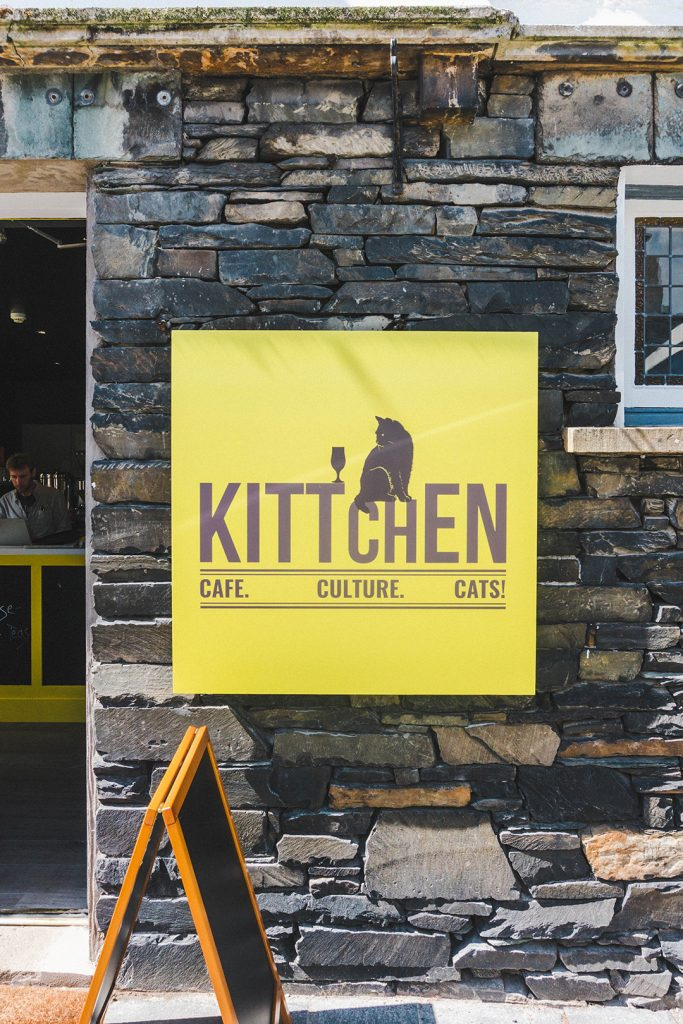 A yellow sign for Kittchen, the only cat cafe in the world that doesn't charge an admission fee, found in the tiny town of Hawkshead, Lake District, UK
