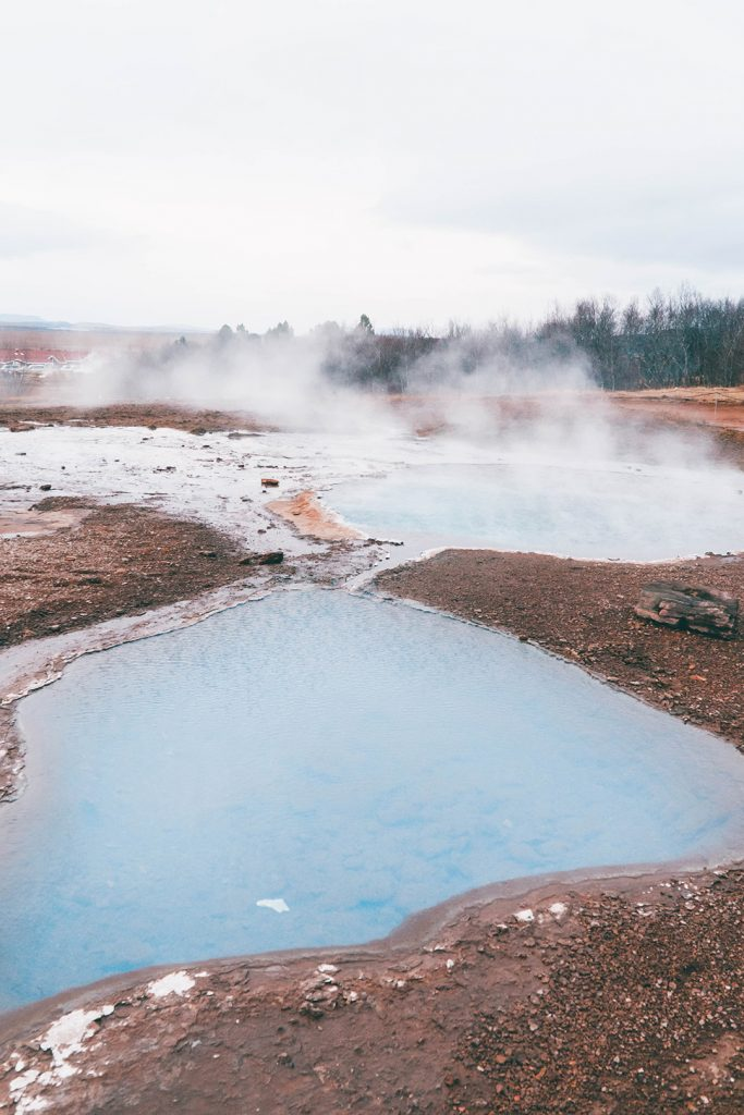 Steam rising from a trio of hot springs at the Geysir Geothermal Area