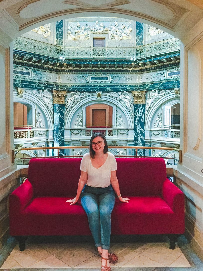 Addie sitting on a red couch in the Art History Museum in Vienna, Austria