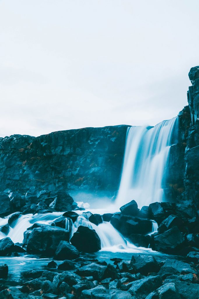 Smooth water falling down towards black rocks at Öxarárfoss Waterfall on our Golden Circle Tour