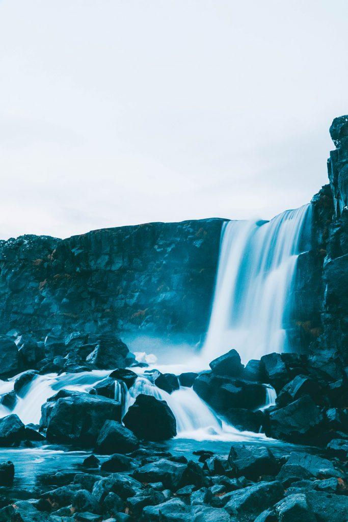 Smooth water falling down towards black rocks at Öxarárfoss Waterfall on our Golden Circle Tour