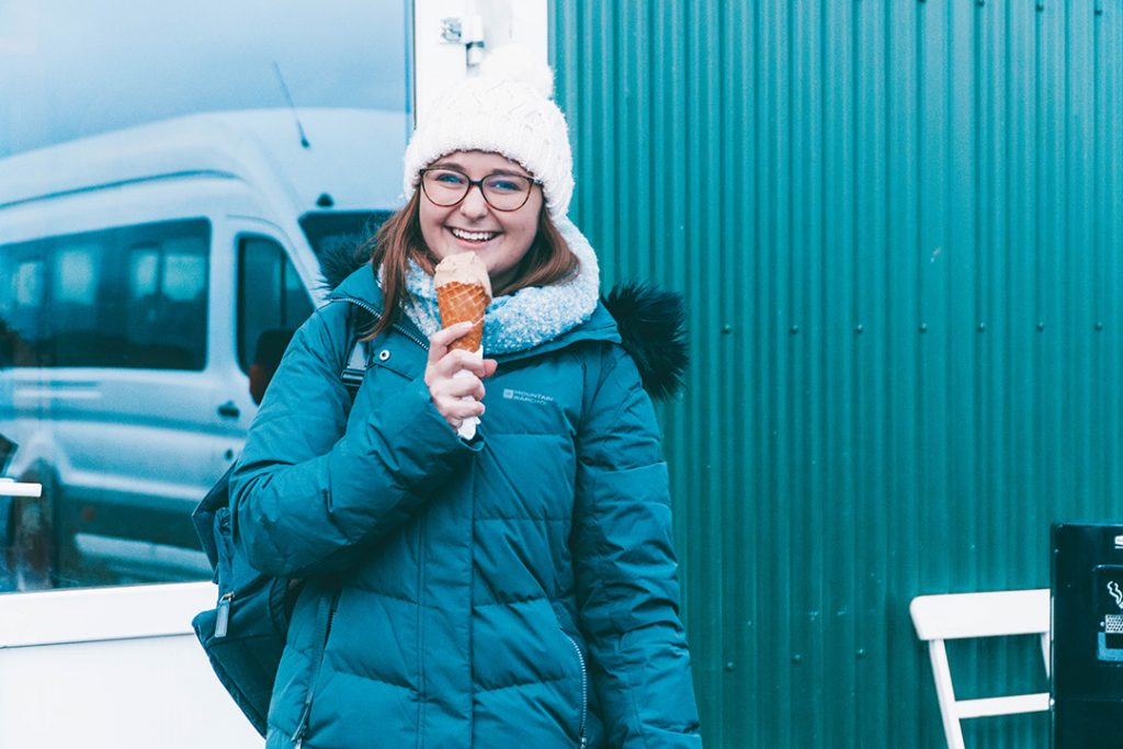 Addie smiling and holding her salted caramel ice cream