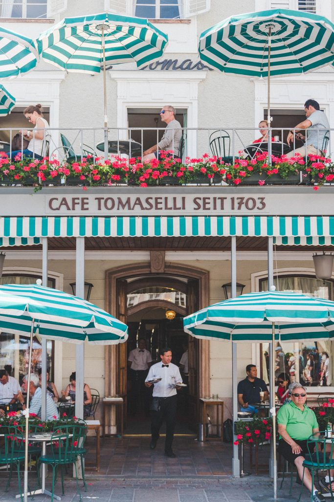 The outside of Cafe Tomaselli in Salzburg, Austria, with adorable green and white striped umbrellas shading outdoor tables