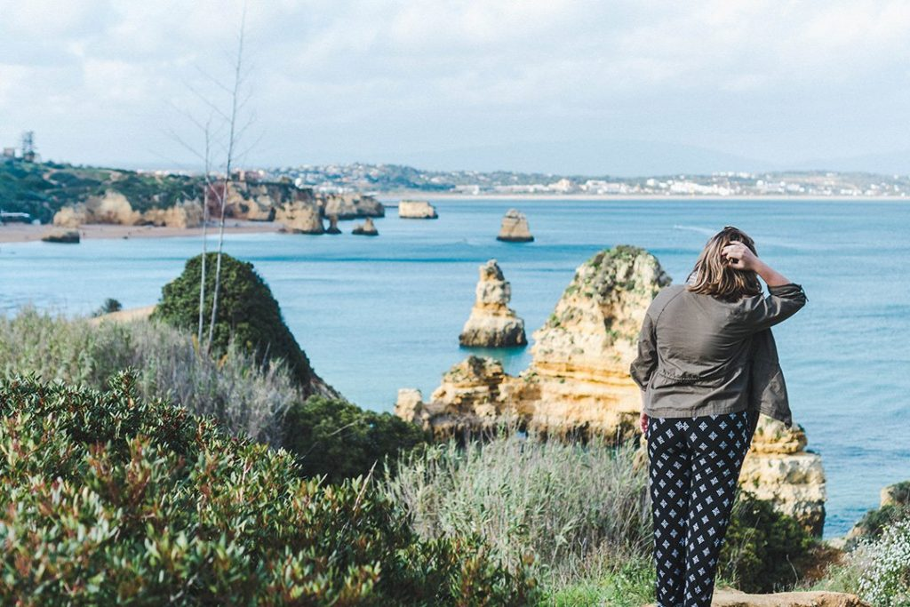 Madison staring out at the cliffs of Lagos, Portugal, a great solo female travel destination