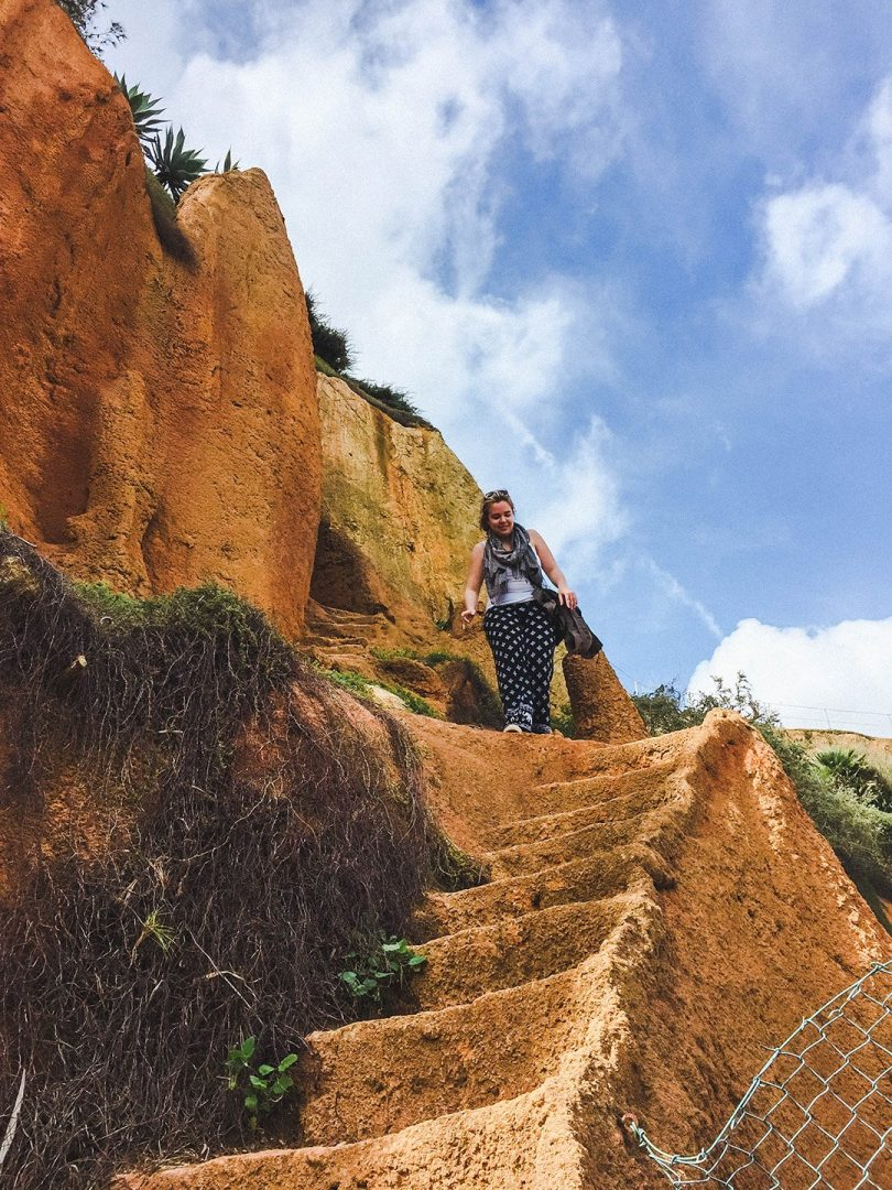 Madison looking scared at walking down a random staircase in the side of the cliffs in Lagos, Portugal