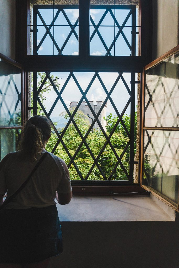 Astrid staring out a window towards the hills in the Salzburg Fortress