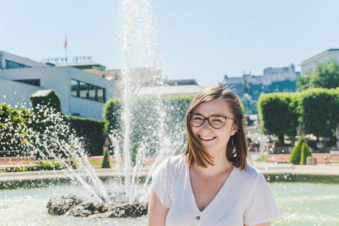 Addie smiling by the fountain in Mirabell Gardens Salzburg, Austria