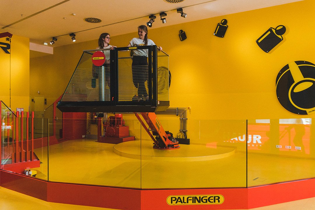 Astrid and Leoni on a mechanical construction lift at the Salzburg Science Museum