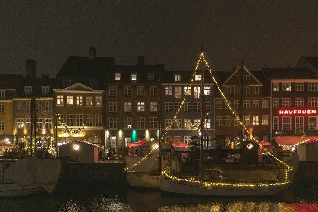 Boats in Nyhavn strung with Christmas lights in Copenhagen, Denmark