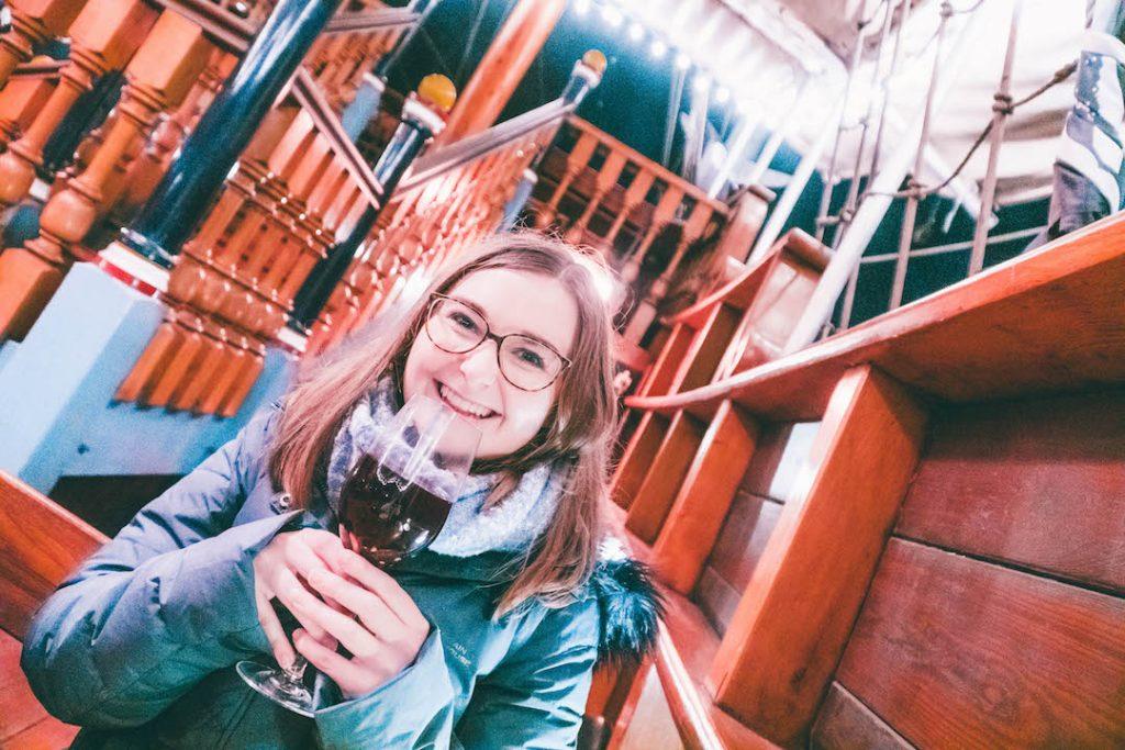 Addie smiling with a full glass of gløgg at the Tivoli Gardens Copenhagen Christmas Market