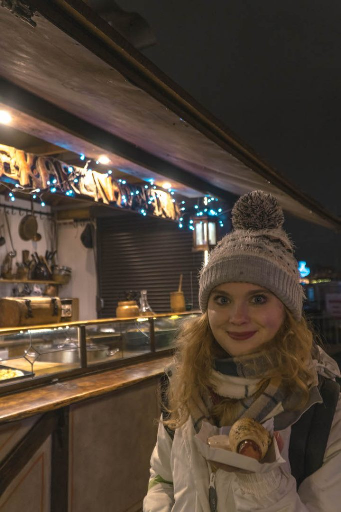 Megan holding a sausage at the Nyhavn Christmas Market
