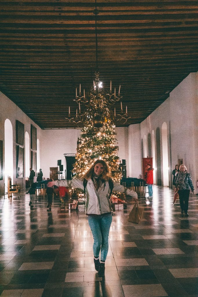 Megan standing in front of the Christmas tree in the Kronborg Castle ballroom