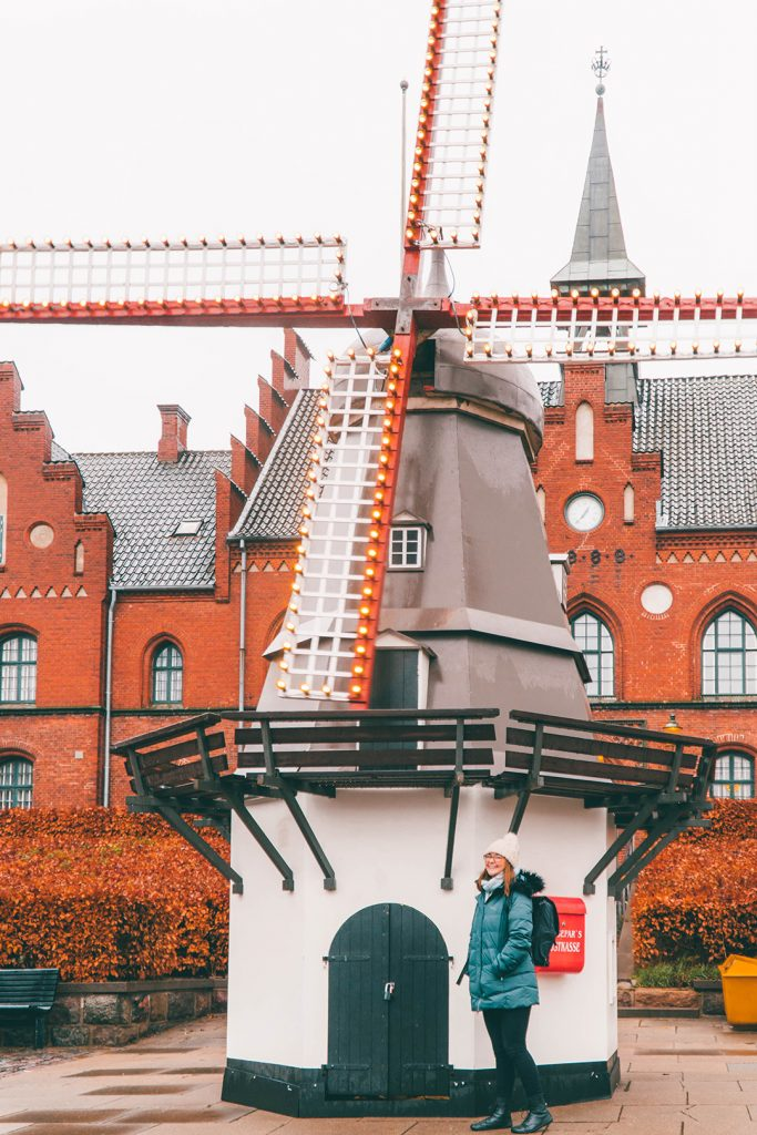 Addie standing in front of a small windmill in Hillerod, Denmark