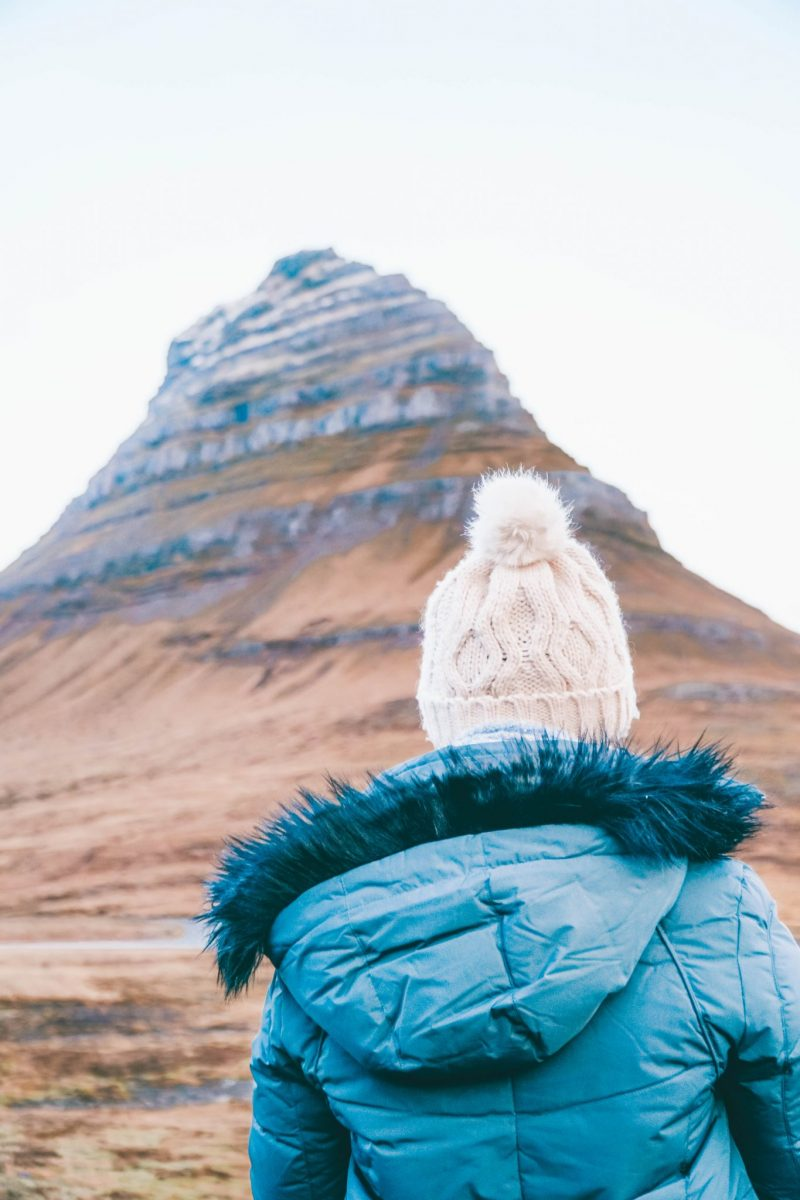 Addie in a pom pom hat looking out at Kirkjufell