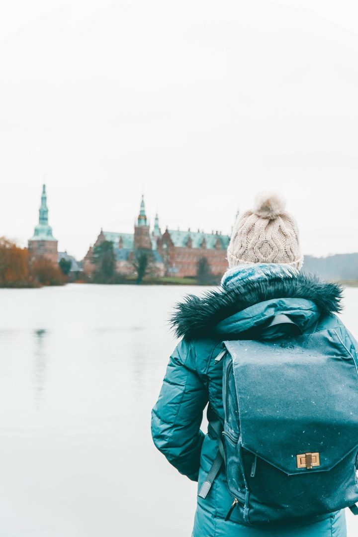 Addie staring across the way at Frederiksbog Castle in Denmark with a camera backpack - travel photography essentials