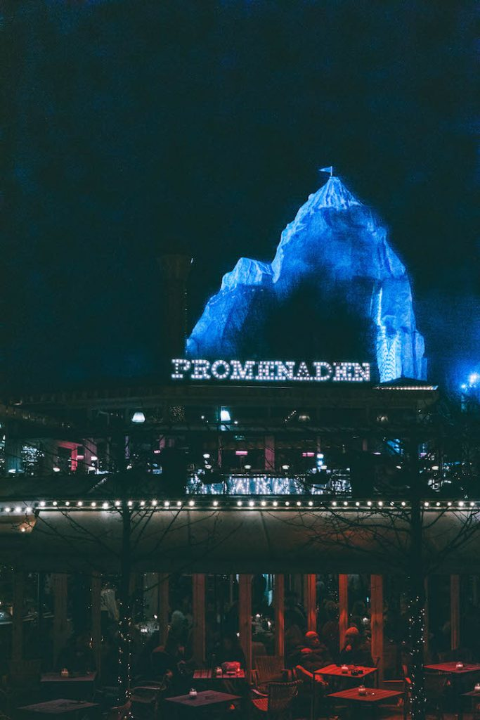 A fake mountain rising up in the background of a lit up scene at Tivoli Gardens Christmas Market