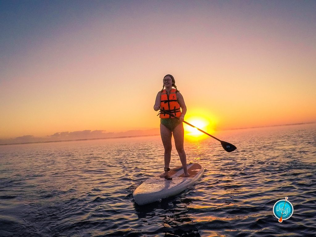 Addie smiling big while standing on a paddlebord during sunrise in Bacalar, Mexico