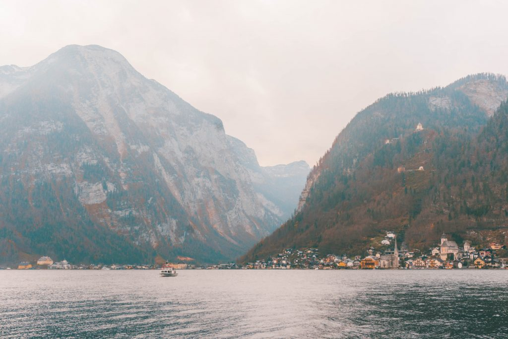 Hallstatt from the other side of the lake: a small expanse of buildings with huge mountains towering behind them.