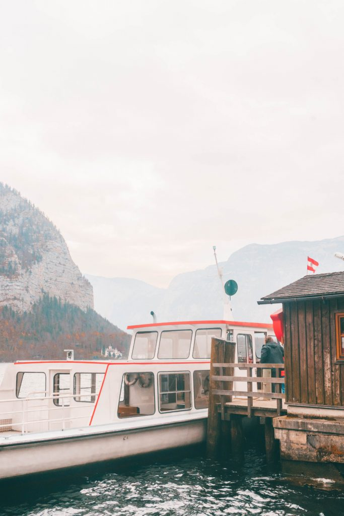 The Hallstatt ferry next to a small wooden boathouse with mountains in the background