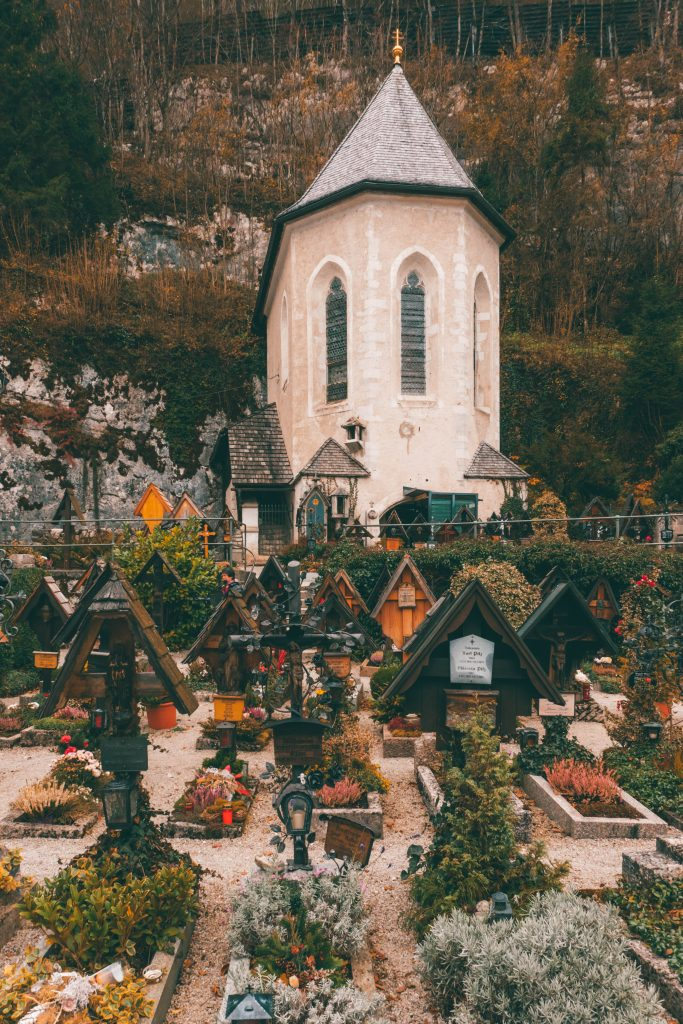 A small graveyard with wooden crosses marking the grave in front of a small church in Hallstatt, Austria