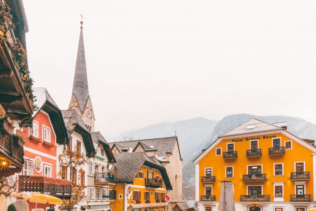 Hallstatt's main square with several colorful houses and a church spiring peeking out from behind them