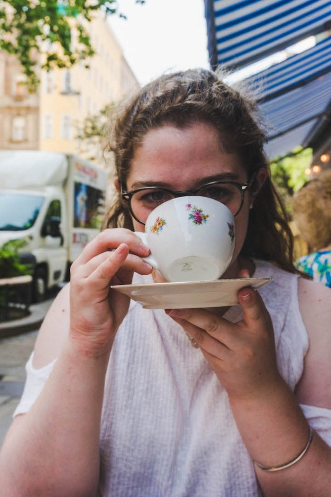 Angela drinking a melange (coffee) from a cafe in Vienna.