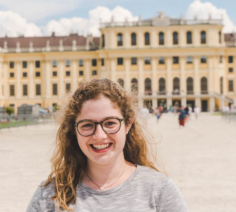 Angela smiling in front of Schonbrunn Palace in Vienna, Austria during her study abroad semester