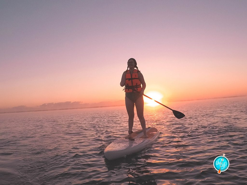 addie on a stand up paddleboard at sunrise in bacalar mexico, one of the best solo female travel destinations