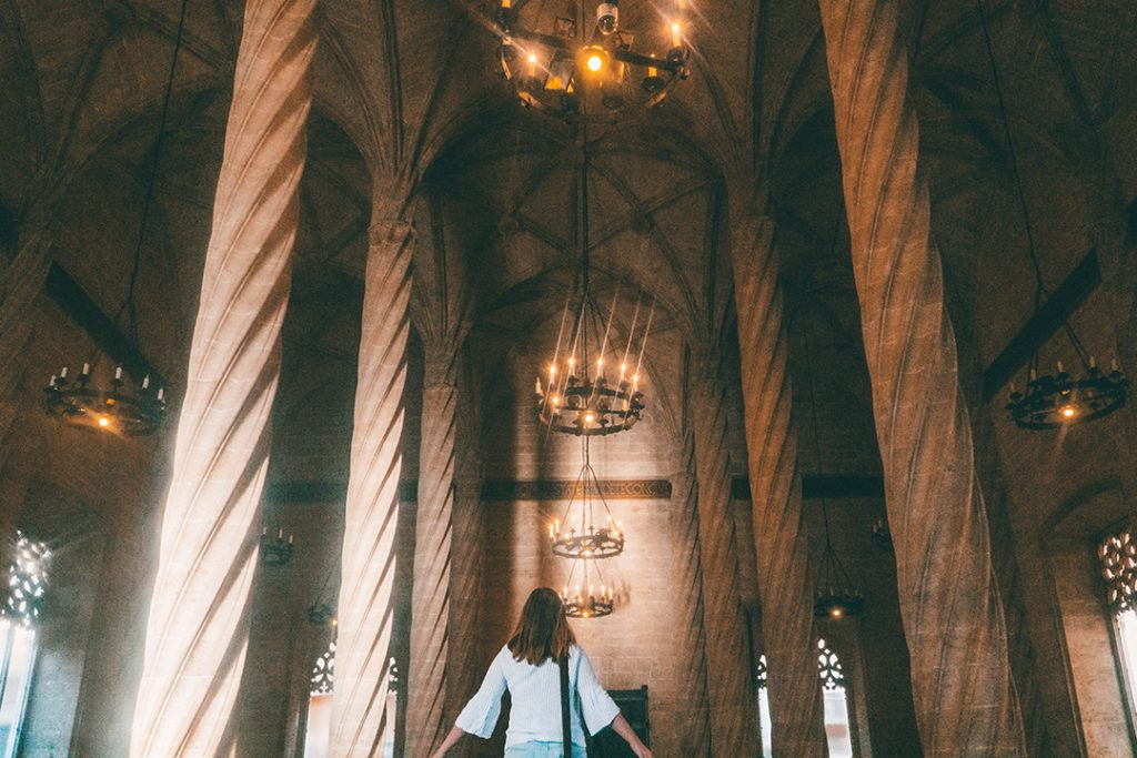 Addie gazing up at the spiraling columns and cathedral-like ceilings of La Lonja in Valencia, Spain