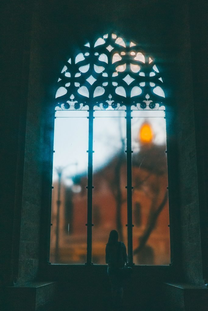 Addie standing looking out of a huge window in La Lonja