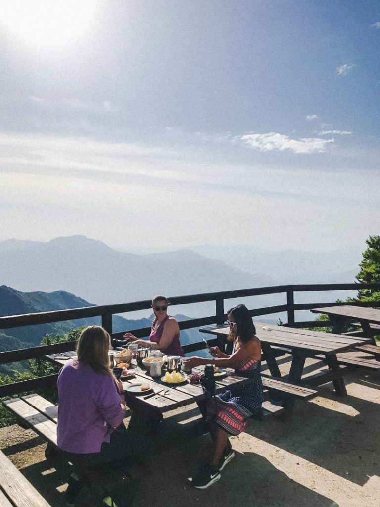 Girls eating breakfast at a picnic table overlooking some mountains