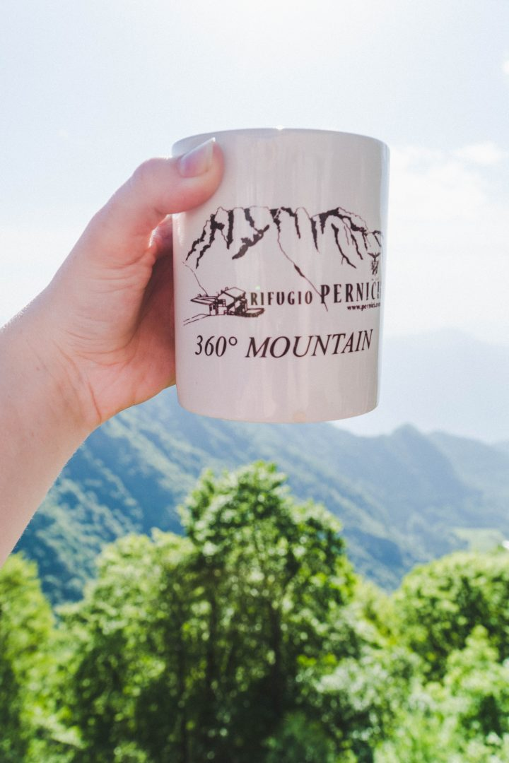 A hand holding a mug from Rifugio Pernici in front of a mountainous background