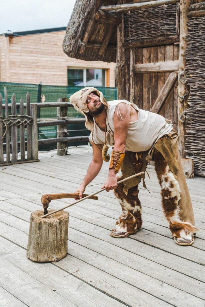 Bacmor, a man dressed in furs and linen, chopping firewood with a small axe