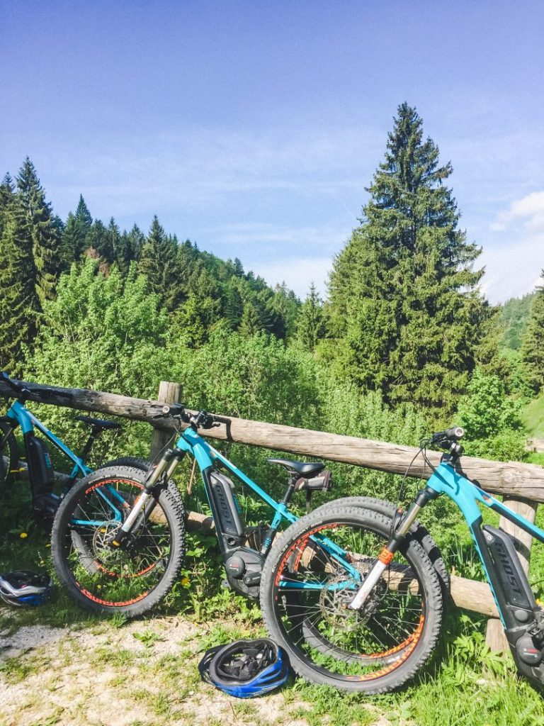 Blue mountain bikes lined up along a wooden fence in the mountain