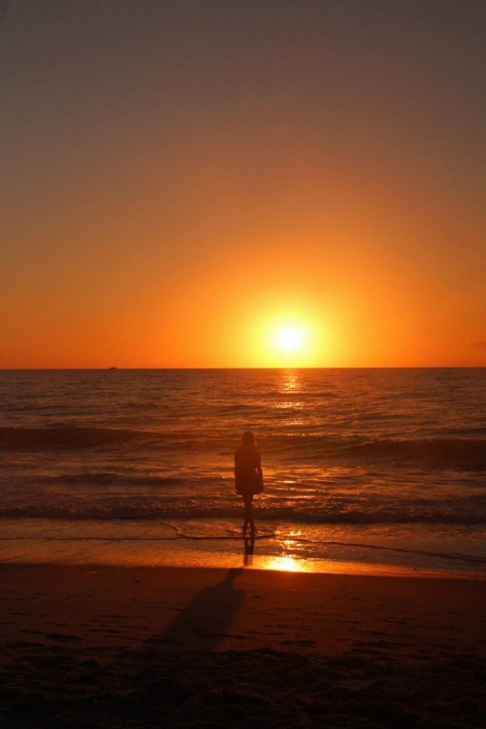 A girl silhouetted by sunset on a beach