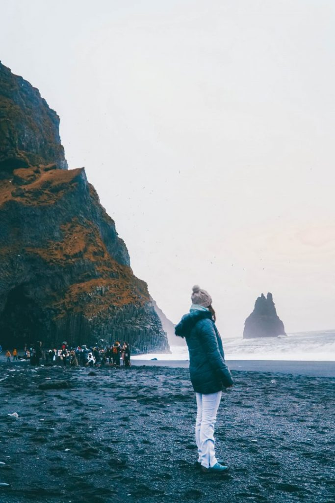 Addie standing on a black sand beach in Iceland, a crowd in the background