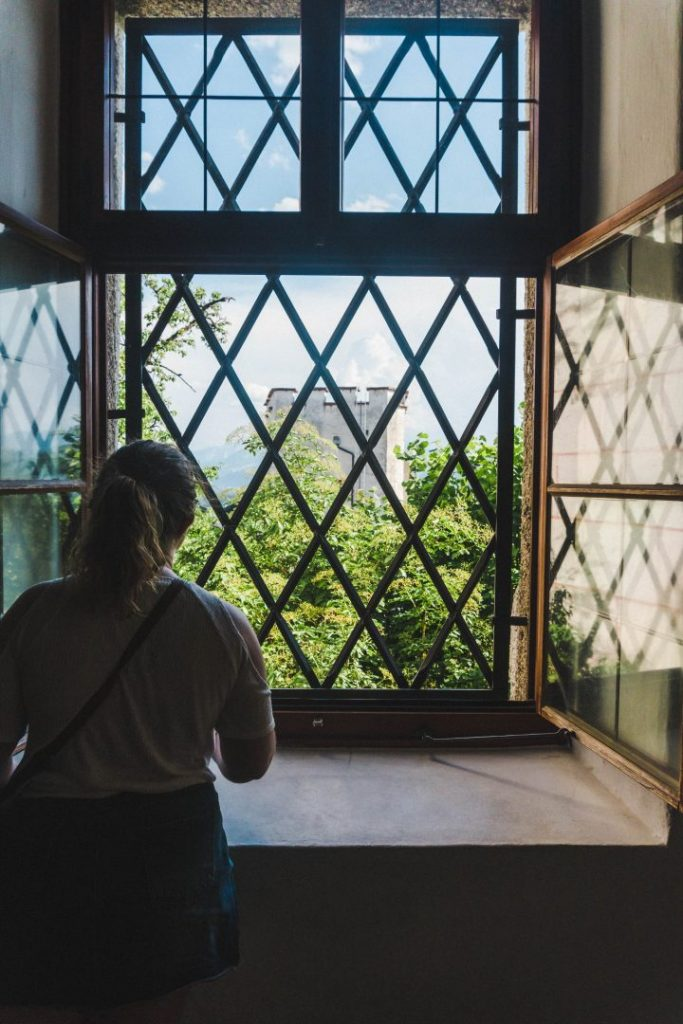 Astrid staring out a window at a castle tower in Salzburg, Austria
