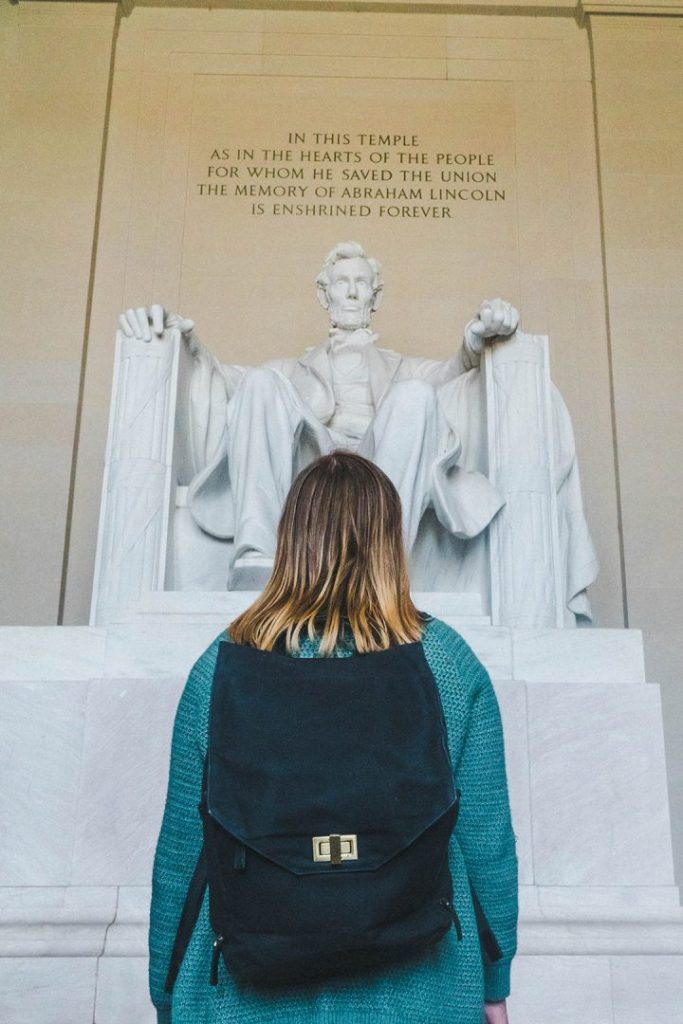 Addie in a green sweater and black backpack staring up at the statue of Abraham Lincoln in the Lincoln Memorial in Washington DC